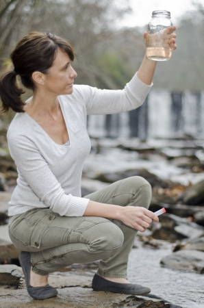 place of research: Female researcher testing the water quality in a river