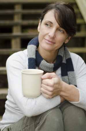 Attractive woman taking a coffee break and thinking over her day photo