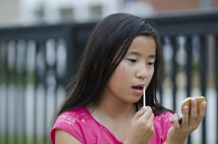 gloss: Pretty young Asian girl concentrating on applying lip gloss