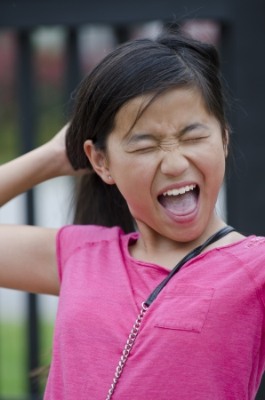 going crazy: Young Asian girl screaming as she pulls her hair