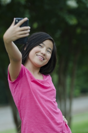 Young Asian girl taking a [self portrait with a cell phone camera Stock Photo