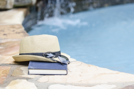 hat, glasses and a book by the pool side