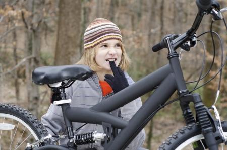 Young kid fixing something on his bike