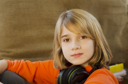 Young teen boy sitting with head phones on his neck