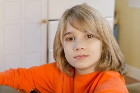 young pre-teen boy sitting comfortably and looking into the camera Stock Photo