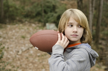Young kid practicing throwing a football outside