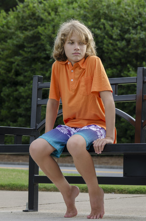 agrivated young man is seated on a bench thinkig about stuff photo