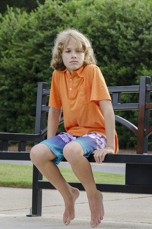 You boy sits patiently on a bench for his friend photo