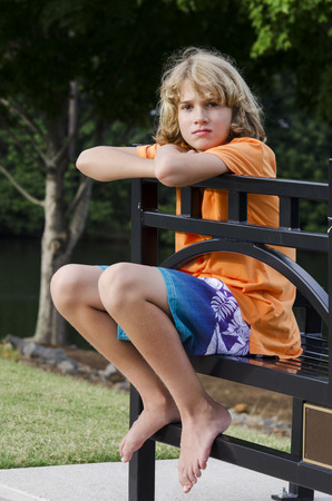 young man waiting on a bench for his ride to pick him up photo