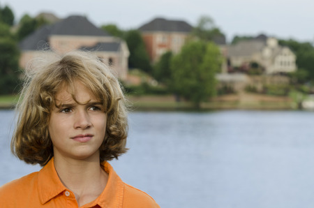 Boy from a wealthy family poses by the lake in their community Reklamní fotografie