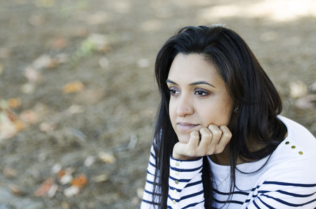 Frustrated young Indian woman contemplating her thoughts Stock Photo