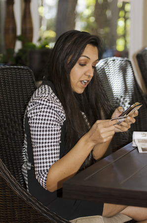 Young Indian woman looks with surprise at her mobile order photo