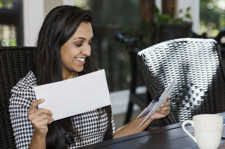 pay bill: Young business woman looking through a stack of mail