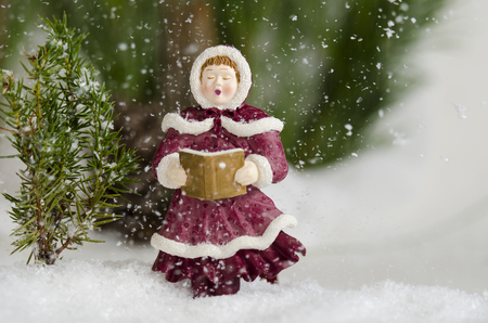 Caroler sing in the snow fall Фото со стока