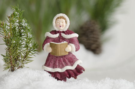 Christmas ornament caroler singing in the snow Stock Photo