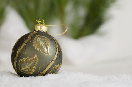 Green and gold ornament in the snow