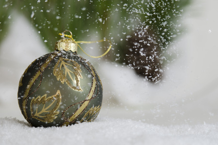 Green and gold ornament in the snow fall Stock Photo