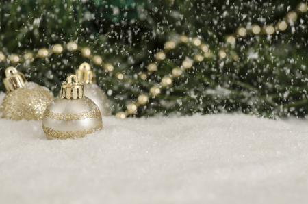 Ornaments by a tree in the falling snow Stock Photo