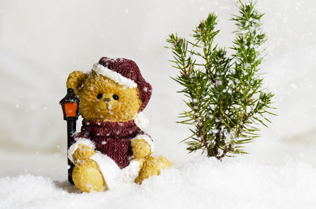 Christmas bear ornament in the falling snow