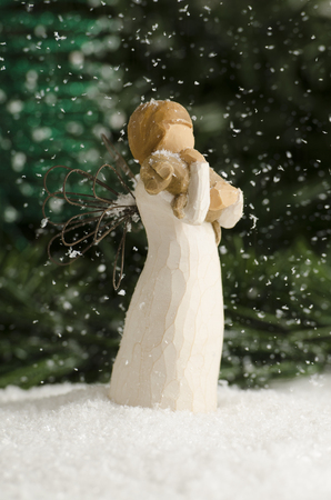 Christmas angel holding a puppy in the snow fall