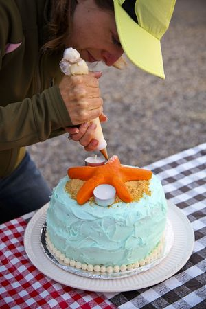decorating: Woman decorating cake with starfish, outdoors on a picnic table. Vertically framed shot.