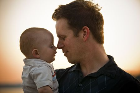 Father and baby touching noses at sunset. Horizontal. Stock Photo