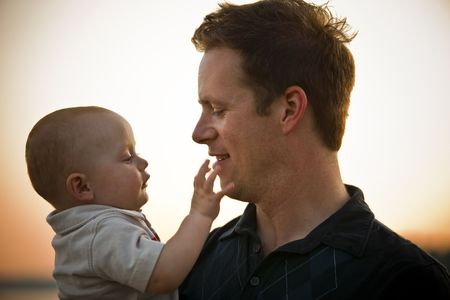 Father and baby at sunset, with baby touching fathers chin. Horizontal.
