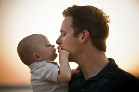 adult baby: Father and baby at sunset, with father about to kiss baby. Horizontal.