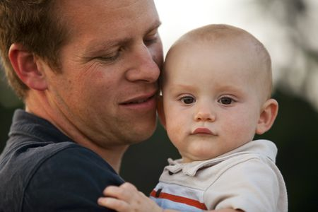 Close-up of father holding baby. Horizontal. photo