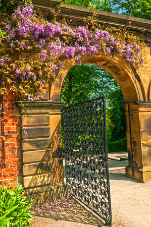 Garden Stone Arched Gateway Surrounded by Flowers photo