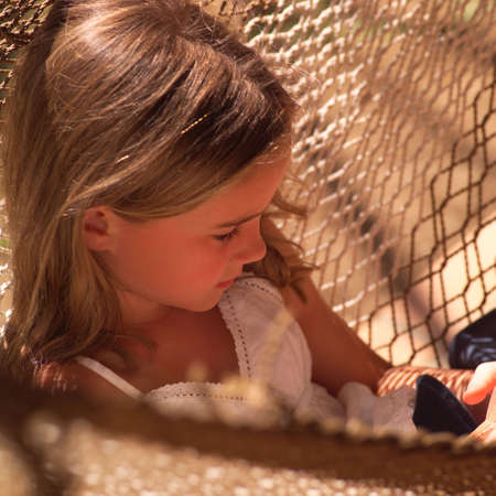 seven year old: Vacationing in Costa Rica,Seven year old girl sitting in a hammock