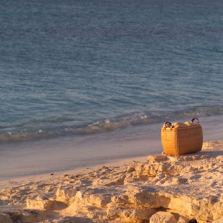 cay: Parrot Cay,Basket on the beach at Parrot Cay Stock Photo