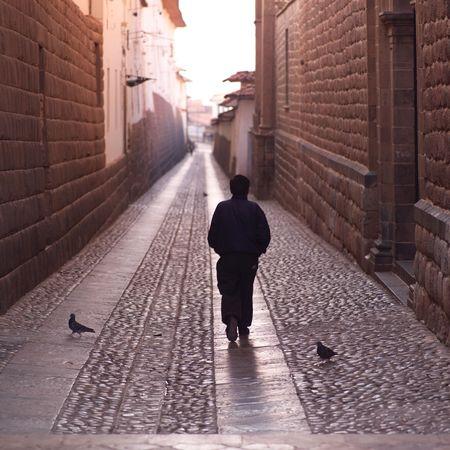 Cusco Peru, Man walking down narrow street