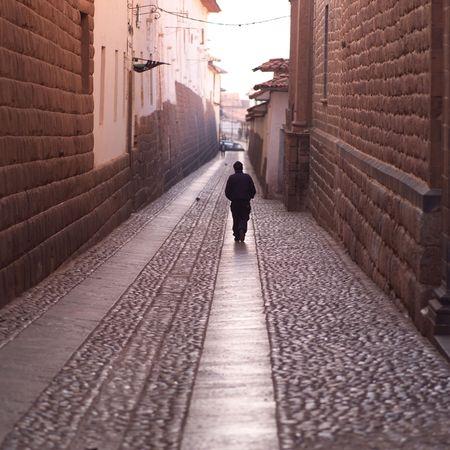 Cusco Peru, Man walking down narrow street photo
