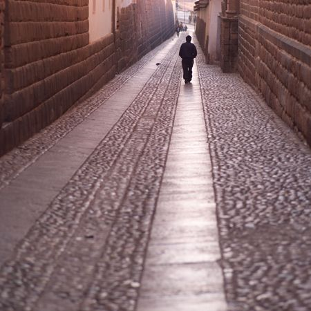 Cusco Peru, Man walking down narrow street