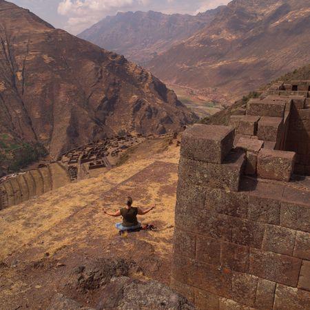 pisaq: Ruins of Pisaq - Temple of the Sun in Peru, Woman in a yoga position Stock Photo
