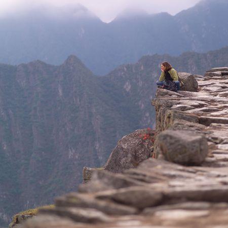 Peru - Machu Picchu, Woman sitting on the edge of a mountain