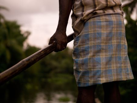 背水、ケララ州、南インドに彼のボートを漕ぐ人