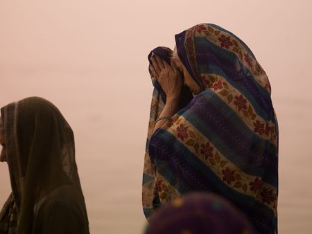 Women praying at the Ganges River in India photo
