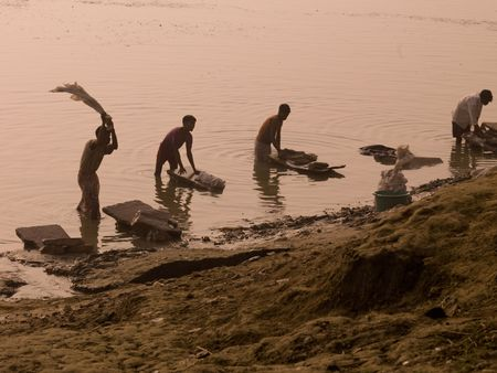 People washing cloths in the Ganges in India photo