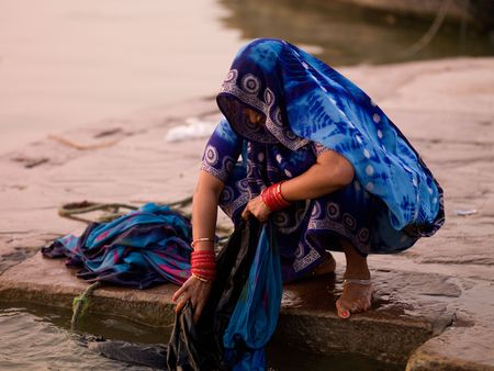 ganges: Woman washing coths in the Ganges River, India