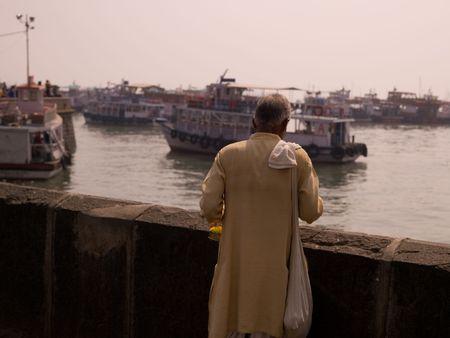 Man standing by riverway in Mumbai India