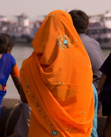 Back of a woman wearing an orange sarong in Mumbai