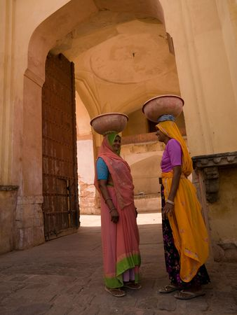 Two women balancing containers on their heads in India