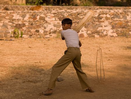 cricket bat: Young boy in India holding a cricket bat