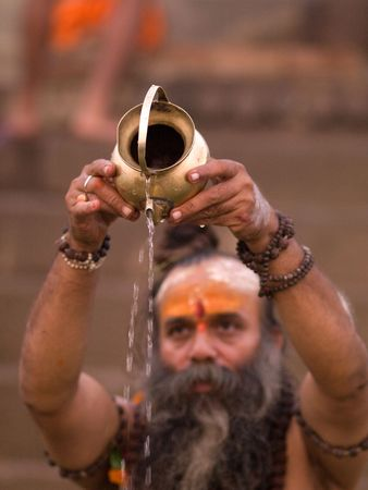 Bearded man in India pouring water out of a container
