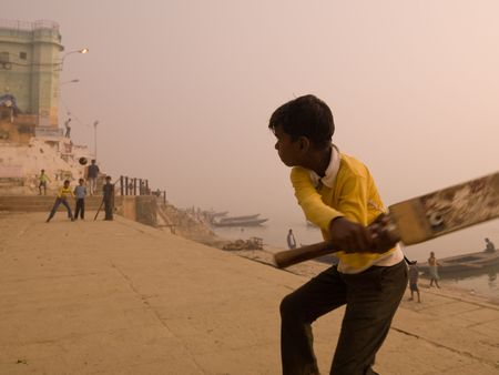 cricket game: Young boy in India holding a cricket bat