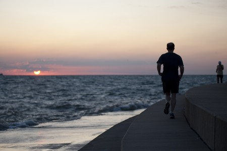 sunup: Man jogging at Chicago, Lake Michigan Stock Photo
