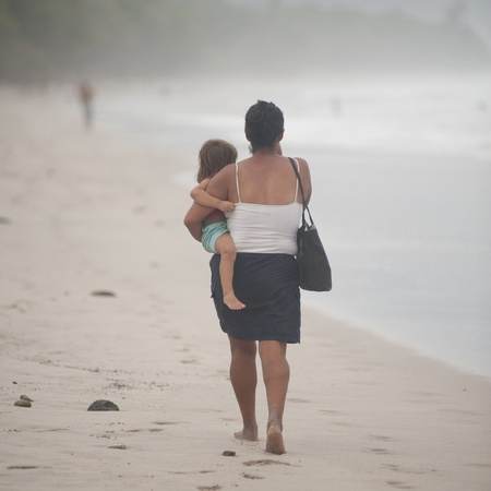Woman carrying a child on the shoreline in Costa Rica photo
