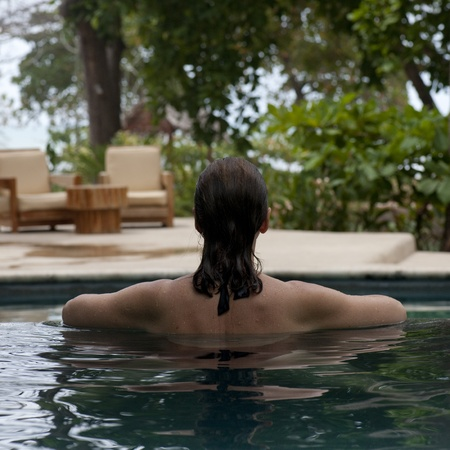back straight: Back view of a brunette woman in a pool in Costa Rica Stock Photo